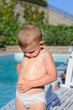 Little boy rubbing sunscreen onto his skin