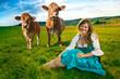 Frau im feld mit kuhen im hintergrund