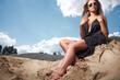 Beautiful girl wearing black dress sitting on the sand