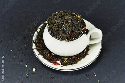 Tea cup on a dish and tea leaves
