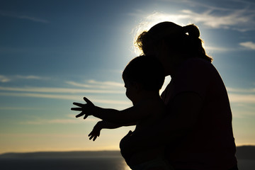 Silhouettes - woman & child playing against sky