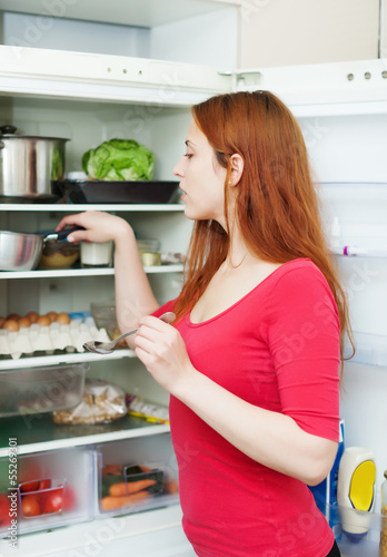 Red-haired woman looking for something in the fridge