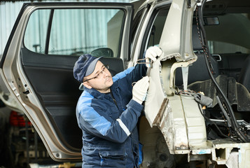 Male auto mechanic repairing body car