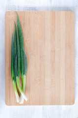 Overhead view of spring onion on wooden board, food background