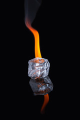 Ice cube with flame on shiny black surface