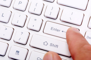 Finger with a computer keyboard.