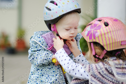 Little girl hepling her sister to put a helmet