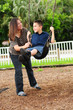 mother and son at park on swing