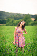 Beautiful young woman enjoying fresh air outdoors in a meadow