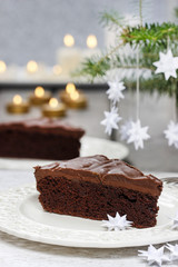 Piece of chocolate cake in white christmas table setting