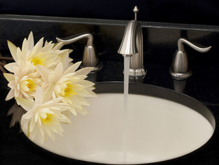 Working water tap and a few water lilies on a sink