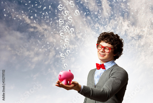 Young businessman holding moneybox