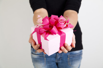 pink gift box with ribbon in woman hands