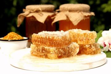 miele con favi su tavolo bianco sfondo foglie verdi