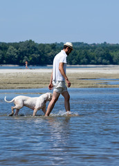 Owner and his dog walking in shallow water