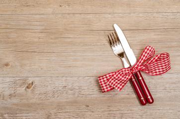 Rustikaler Tisch aus Holz mit Messer und Gabel in rot