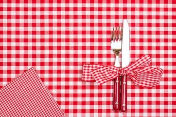Messer und Gabel mit Schleife und Serviette auf rot karierten Tu