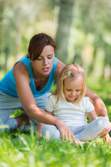 Mother and daughter doing exercise outdoors