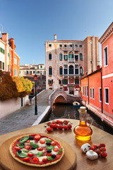 Venice with Italian pizza against canal in Italy