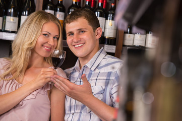 Young couple degustating red wine at supermarket
