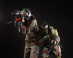 Studio shot of two paintball players over black background