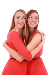 Two girls twins in red dresses hugging isolated on the white