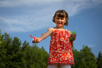 Portrait of funny little girl playing with soap bubbles