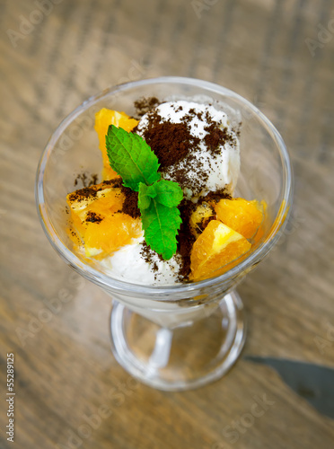 Fresh ice cream with orange and mint in glass