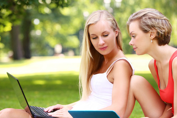 Beautiful girls using laptops at a park