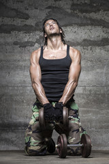 portrait of handsome athlete lifting weights on wall background