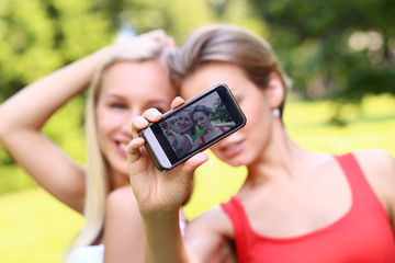 Two girls are taking photos of themselves