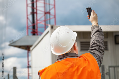 Engineer with the cell phone near to gsm tower - 55292789