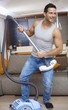 Young man using vacuum cleaner as guitar