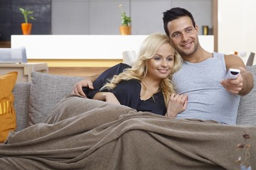 Loving couple watching tv at home
