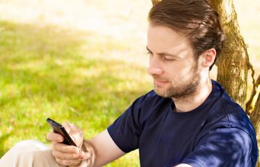 Caucasian man looking at mobile phone outdoor