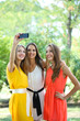 Three beautiful young woman  taking picture in summer park