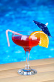 Tasty cocktail on swimming pool background