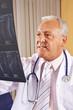 Arzt hält Röntgenbild einer Wirbelsäule