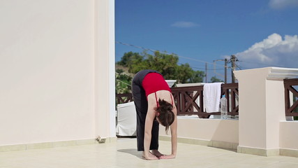 Young woman doing yoga exercise on terrace