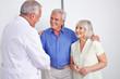 Arzt begrüßt Senioren mit Handschlag