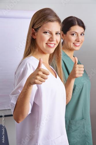 Zwei Krankenschwestern halten Daumen hoch