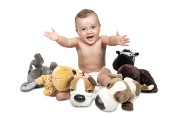 baby boy in the middle of alot of stuffed animals.