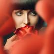 Brunette behind red rose