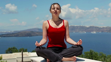 Beautiful young woman meditating outside