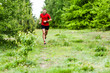 Man cross country running on trail forest