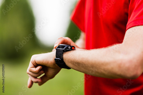 Runner looking at sports watch