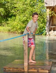 Junge überquert mit einem Floß einen Bach
