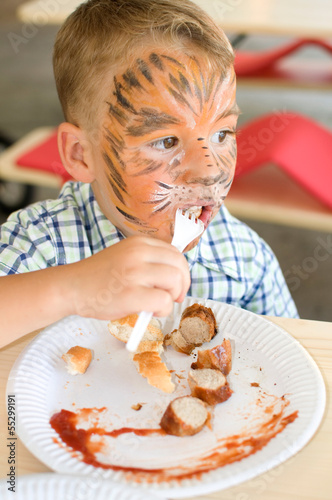 Kleiner Junge beim Bratwurstessen,