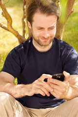 Caucasian man looking at mobile phone outdoor