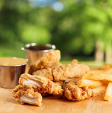 fried chicken strips with french fries and sauce.